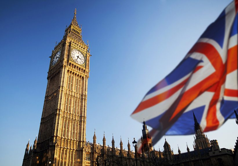 UK flag flying in front of Big Ben and UK Government Building